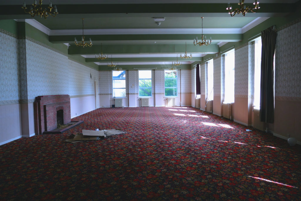 Interior wide shot of Sergeants' Mess ballroom with original 1940s fireplace and large windows