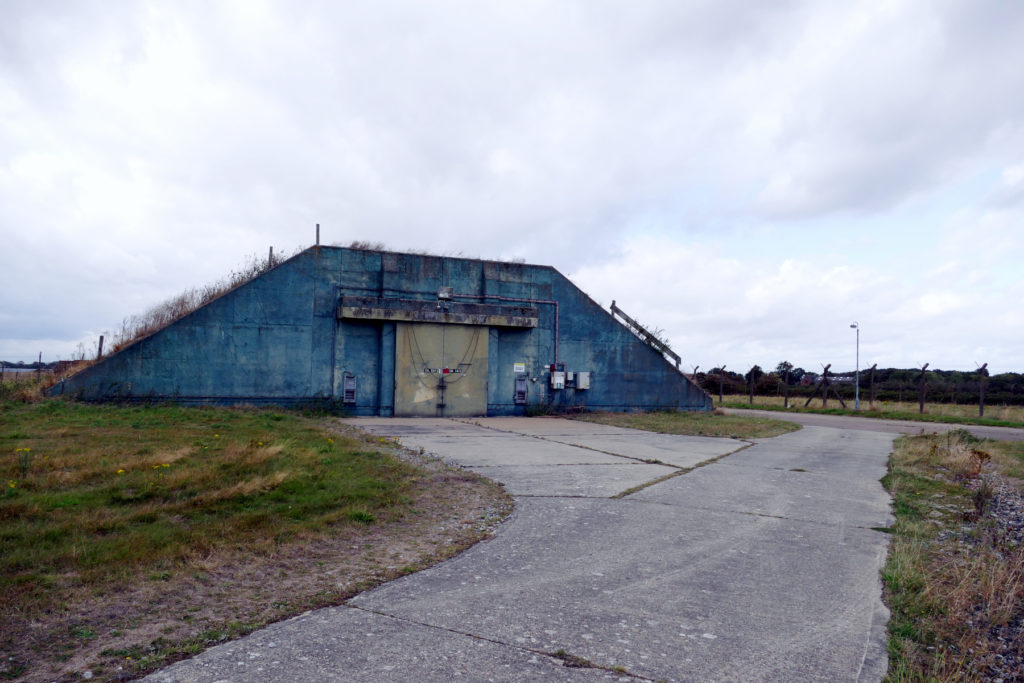 Wide shot of original Cold War bunker with blue walls, green blast door on grass with concrete road