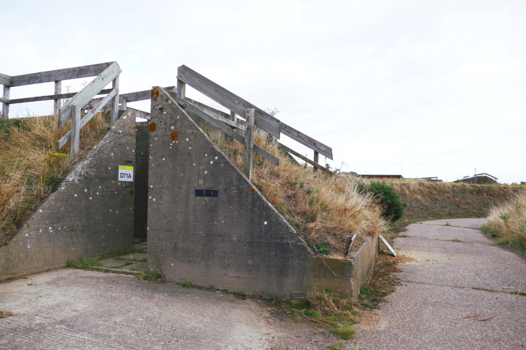 Exterior of old RAF industrial storage unit with concrete walls, concrete road and grass