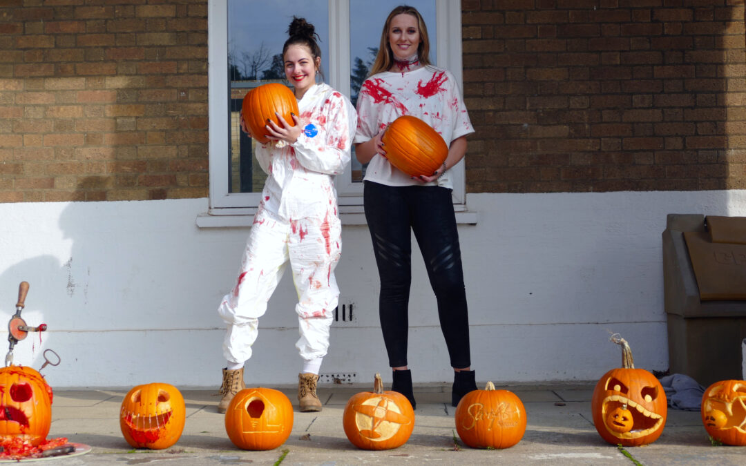 Marie (left) and Phoebe (right) dressed in Halloween costumes holding pumpkins standing behind 2019 carved pumpkin entries